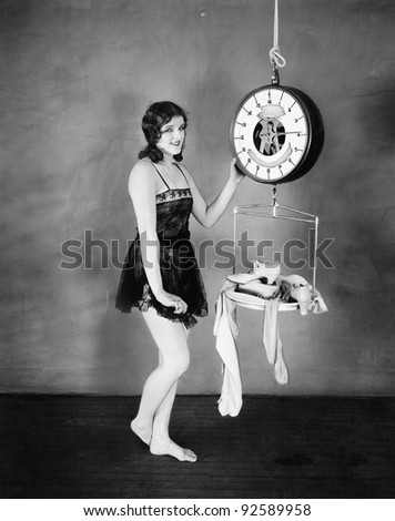 Portrait of a young woman weighing her clothes and sandals on a weighing scale - stock photo