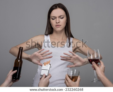 Portrait of a young woman who refuses to alcohol and tobacco. Young girl struggling with her bad habits. - stock photo