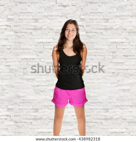 Portrait of a young woman with a beautiful smiling face, she's wearing pink shorts and a black shirt in front of white marble background - stock photo