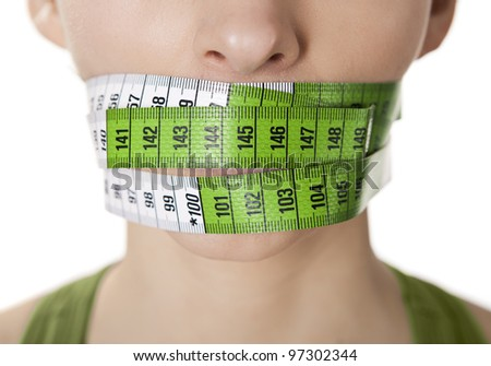 Portrait of a young  woman with a green measuring tape covering the mouth - stock photo