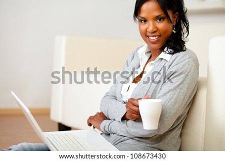 Portrait of a young woman with a mug is looking to you and browsing the Internet on her laptop while is sitting on the floor at home indoor - stock photo