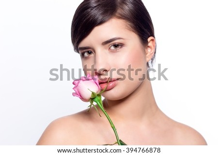 Portrait of a young woman with a rose on a white background. Brunette holding a rose on a white background. Beauty.