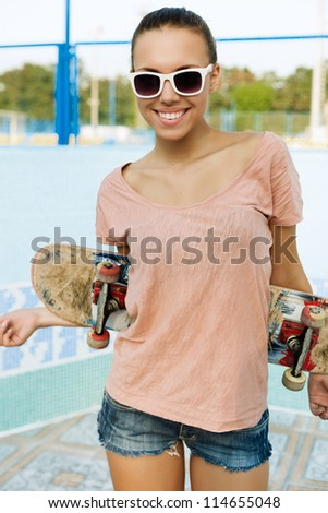 Portrait of a young woman with a skateboard in her hand, outdoors - stock photo
