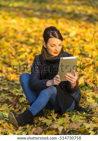 Portrait of a young woman with a tablet sitting in a yellow autumn forest.