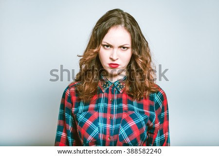 Portrait of a young woman with an angry face isolated on a gray background - stock photo