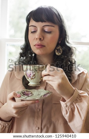 Portrait of a young woman with antique tea cup and saucer.