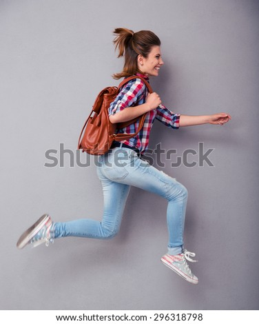 Portrait of a young woman with backpack running over gray background - stock photo