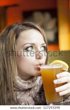 Portrait of a young woman with beautiful blue eyes drinking a pint of hefeweizen beer. - stock photo