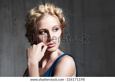 Portrait of a young woman with blonde hair in a cement background - stock photo