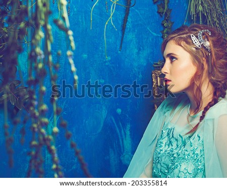 Portrait of a young woman with braid hairstyle on blue grunge texture background - stock photo