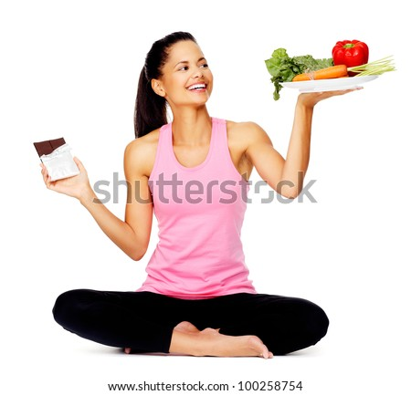 portrait of a young woman with chocolate and vegetables, healthy eating balance scale concept - stock photo