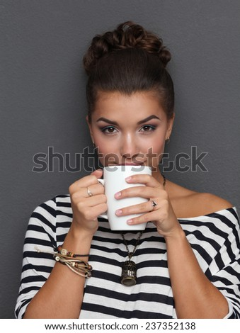 Portrait of a young woman with cup of tea or coffee, isolated. - stock photo