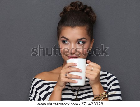 Portrait of a young woman with cup  tea or coffee, isolated on gray background. - stock photo