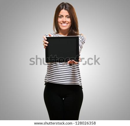 Portrait Of A Young Woman With Digital Tablet against a grey background - stock photo