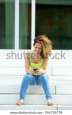 Portrait of a young woman with earphones looking at mobile phone - stock photo