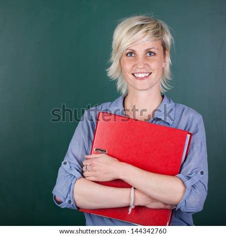Portrait of a young woman with folder in front of chalkboard - stock photo