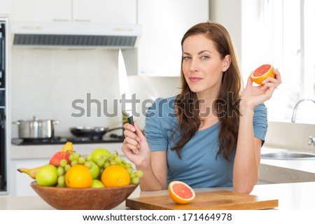 Portrait of a young woman with fruit bowl on counter in the kitchen at home