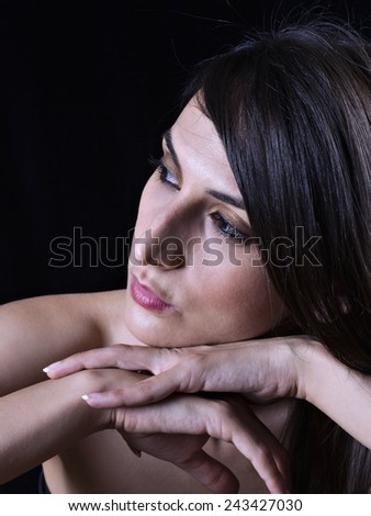 Portrait of a young woman with hands on chin - stock photo