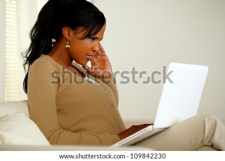 Portrait of a young woman with headache working on laptop at home indoor - stock photo