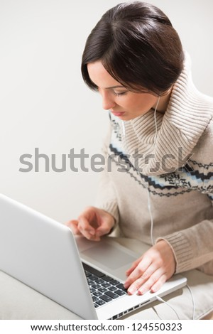 Portrait of a young woman with headphones, lying in front of her laptop and chatting with friends