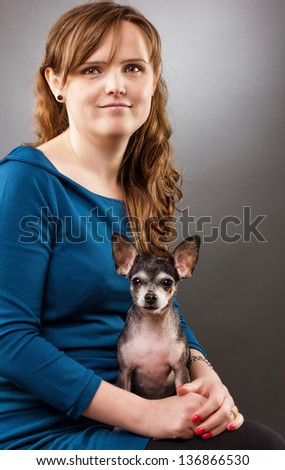 Portrait of a young woman with her chihuahua isolated on white background