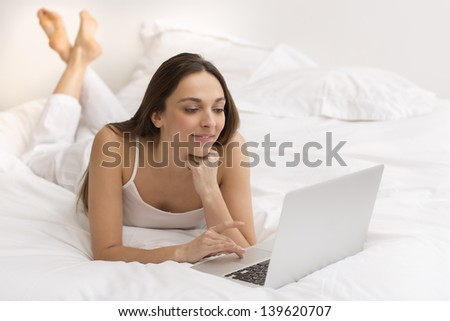 Portrait of a young woman with her computer on the bed