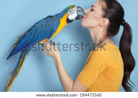 Portrait of a young woman with her domestic ara parrot - stock photo