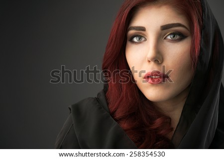 Portrait of a young woman with her hair covered by a black veil - stock photo