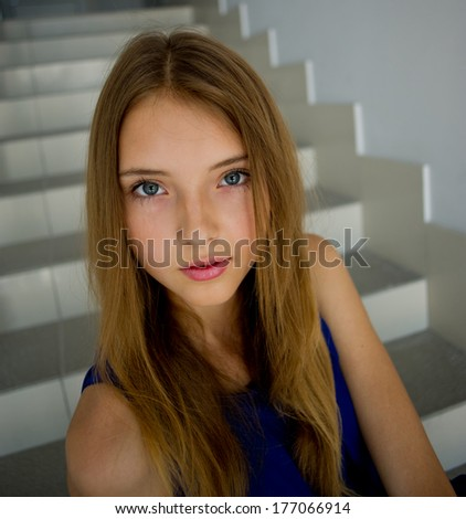 portrait of a young woman with her hair which looks at the camera, indoors