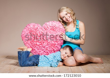 Portrait of a young woman with her son while holding a heart shape sign - stock photo