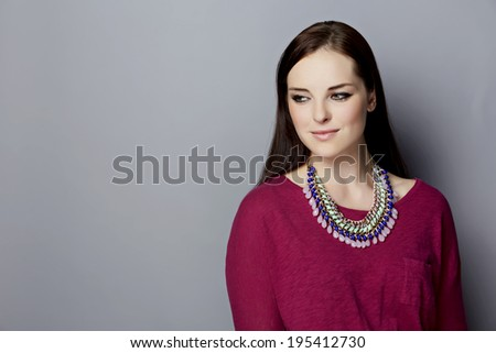 Portrait of a  young woman, with long brunette hair, on gray studio background, wearing pink purple top and bright statement necklace with space for text - stock photo