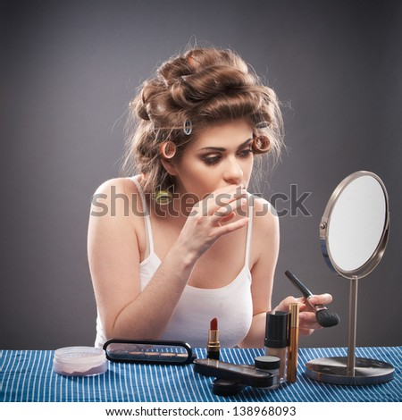 Portrait of a young woman with long curly hair on gray background isolated. Female Model Seating at table applying make up