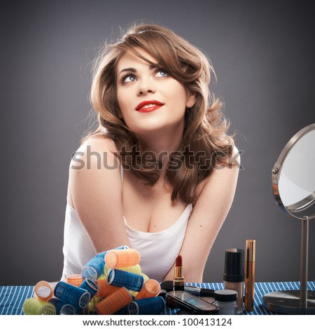 Portrait of a young woman with long hair on gray background isolated.  Happy girl seating at table with make up accessories and mirror. Smiling model with curler hair dress - stock photo