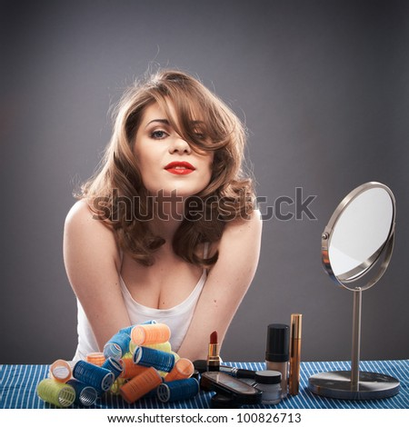 Portrait of a young woman with long hair on gray background isolated.  Happy girl seating at table with make up accessories and mirror. Smiling model with curler hair dress