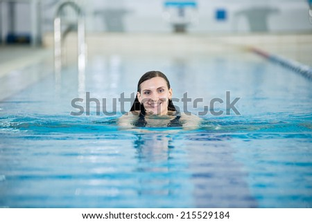 Portrait of a young woman with long hairs in swimming pool. Relaxing after fitness exercises. Indoor sport pool with blue water.