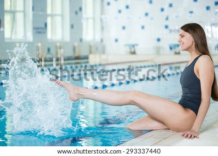 Portrait of a young woman with long hairs near swimming pool. Relaxing after fitness exercises and splashing water. Indoor sport pool with blue water. - stock photo
