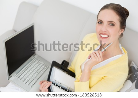 Portrait of a young woman with personal organizer and laptop at home