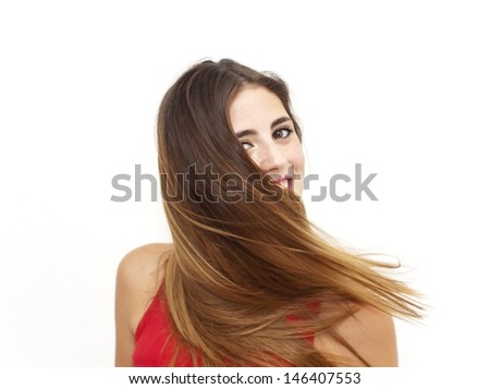 Portrait of a young  woman with red shirt and her hair in the wind over white background