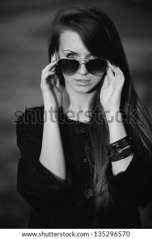 portrait of a young woman with sunglasses, black and white