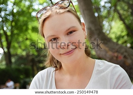 Portrait of a young woman with sunglasses on head - stock photo