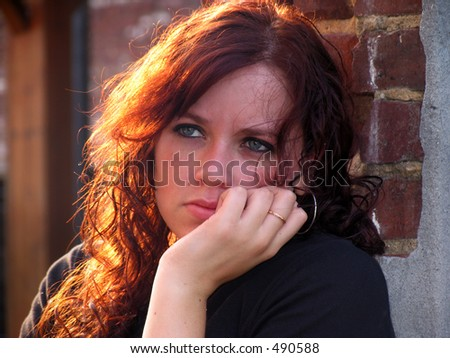 Portrait of a young woman with sunlit hair and sad expression - stock photo