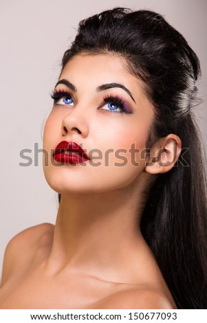 portrait of a young woman with tanned skin, blue contact lenses and red lipstick wearing long brown hair loose over studio background
