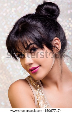 portrait of a young woman with tanned skin, long brown hair in a bun over glitter studio background with space for text