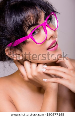 portrait of a young woman with tanned skin, long brown hair in a bun with pink glasses over gray studio background - stock photo