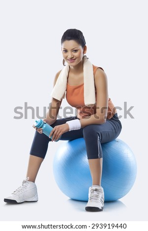 Portrait of a young woman with towel round shoulders sitting on a fitness ball over white background - stock photo