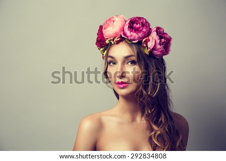 Portrait of a Young Woman with Wreath of Pink Flowers on Gray Background. Natural Beauty Concept. Toned Photo with Copy Space.
