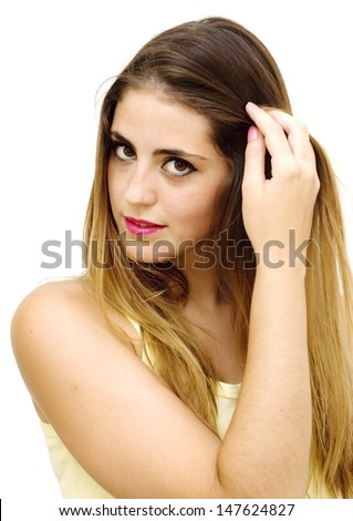 Portrait of a young  woman with yellow shirt touching her hair over white background