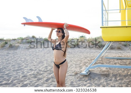 Portrait of a young women dressed in trendy swimwear going to the beach with her surfboard, surfer female in bikini with perfect body preparing for swimming in the sea during beautiful summer weekend - stock photo