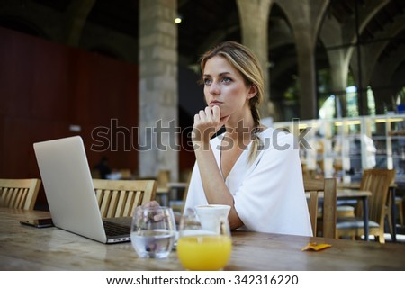 Portrait of a young women thinking about something while sitting front portable laptop computer in modern cafe interior, beautiful dreamy female taking break between work on net-book during breakfast - stock photo