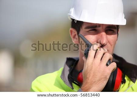 Portrait of a young worker with noise-canceling headphones - stock photo